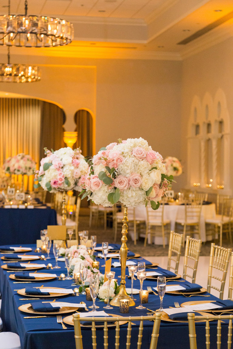 Southern Charm Hotel Ballroom Wedding Reception with Tall White and Pink with Greenery Centerpiece in Gold Candelabra Vase, with Gold Chiavari Chairs and Chargers, Navy Blue Linens and Tablecloth | St Pete Historic Hotel Wedding Reception Venue The Vinoy Renaissance