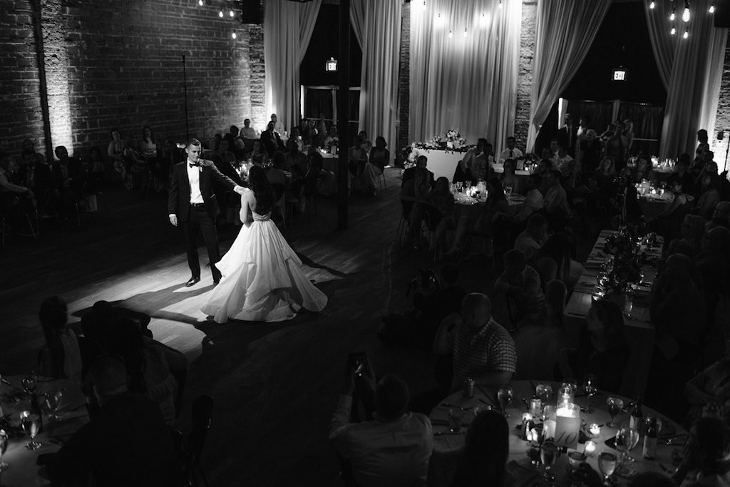 Wedding Reception First Dance Portrait with Exposed Brick Wall and Hanging Edison Bulb Lights   Unique Downtown St Pete Wedding Venue NOVA 535