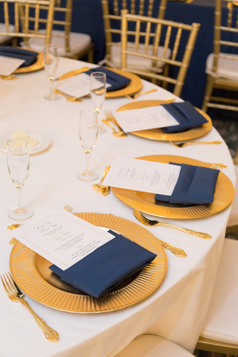 Southern Elegance Wedding Reception Round Table Setting with Gold Chargers, White Printed Menus in Navy BLue Napkins, Blush Linens, and Gold CHiavari Chairs and Flatware