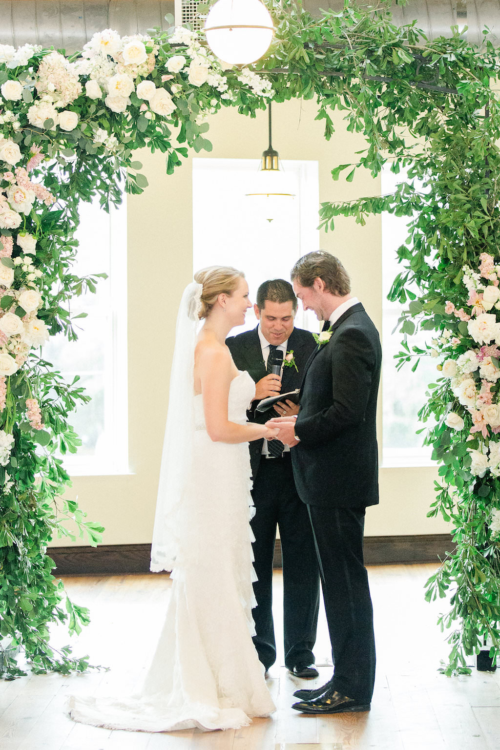 Indoor Industrial Garden Wedding Ceremony Portrait, with Greenery and White Floral Arch   Tampa Bay Wedding Photographer Ailyn La Torre   Venue The Oxford Exchange