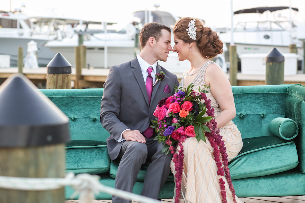 Outdoor Dockside Waterfront Wedding Reception Portrait, Bride in Jeweled Ivory Dress, Groom in Gray Suit with Fuchsia Tie and Pocket Square and Plum Boutonniere, with Pink, Purple Floral and Greenery Cascading Bouquet on Turquoise Velvet Lounge Couch | Tampa Bay Waterfront Wedding Venue Isla Del Sol Yacht and Country Club | Dress Shop Truly Forever Bridal | Menswear Sacino's Formalwear | Hair and Makeup Michele Renee The Studio | Photographer Lifelong Studios Photography | Rentals A Chair Affair | Planning Kelly Kennedy Weddings and Events