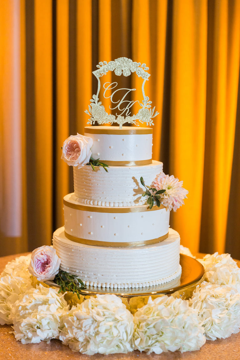 Four Tier Round White with Gold Ribbon Stripes Wedding Cake with Ornate Custom Monogram Floral Framed Cake Topper on Gold Cake Stand with White and Pink Flowers | St Pete Wedding Stationary and Monograms A and P Designs | Historic Hotel Wedding Venue, Caterer, and Cake Vinoy Renaissance