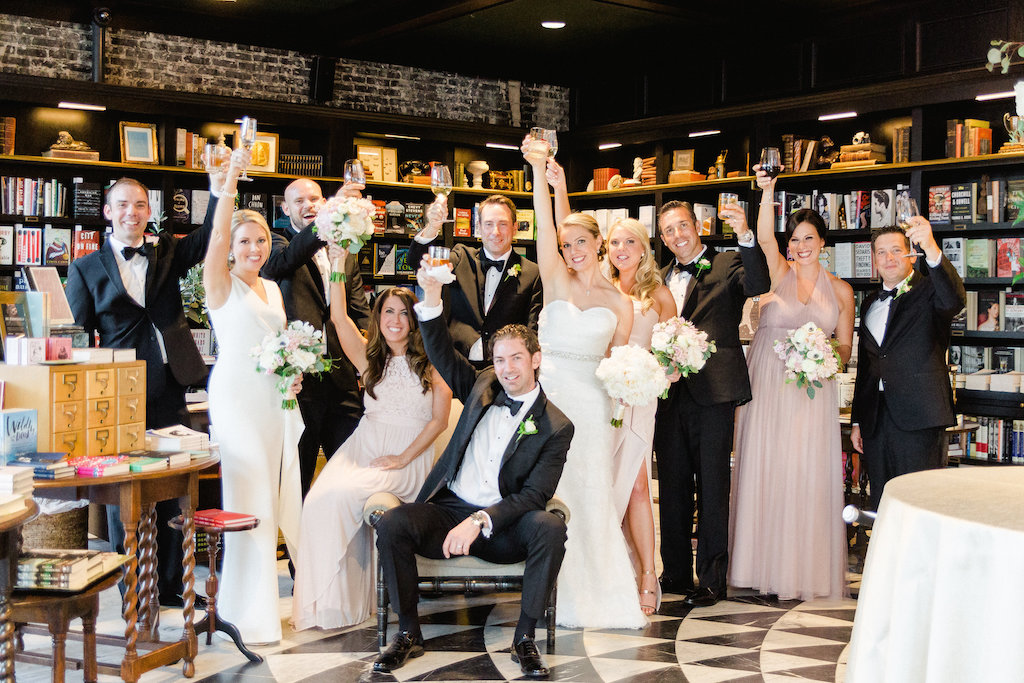 Indoor Wedding Party Portrait in Vintage Bookstore, Bridesmaids in Mismatched Blush Dresses with White Floral and Greenery Bouquets , Groomsmen in Classic Black Tuxedos   Tampa Bay Wedding Photographer Ailyn La Torre Photography   Venue The Oxford Exchange