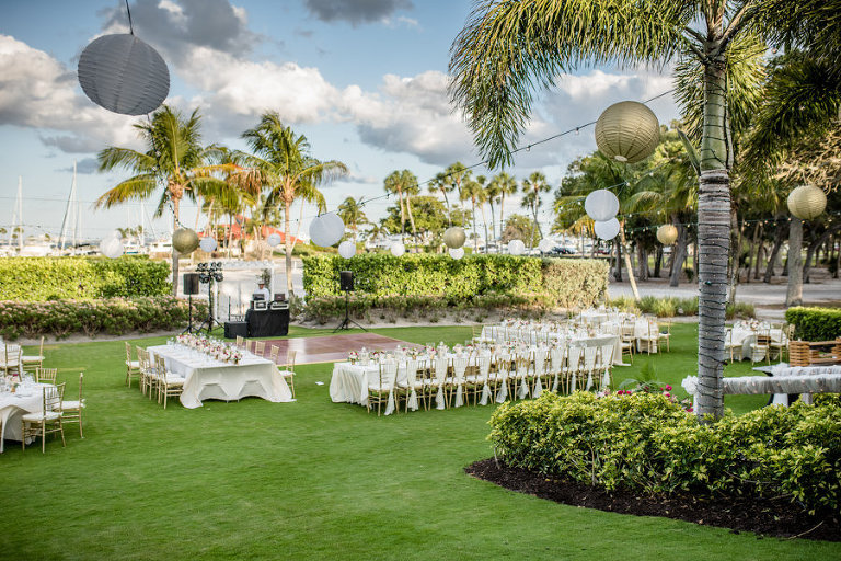 Outdoor Garden Wedding Reception with Long Feasting Tables with White Linen and Gold Chiavari Chairs, Palm Trees Wrapped in String Lights with White and Gold Chinese Paper Lanterns | Sarasota Wedding Planner NK Productions | Venue Lonboat Key Club