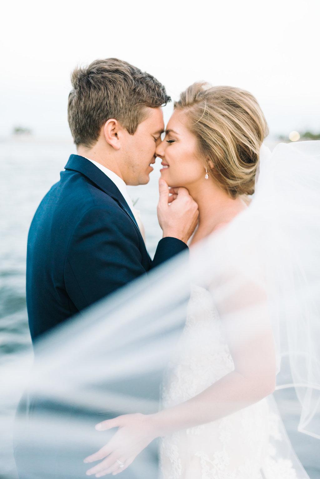 Outdoor Downtown St. Pete Waterfront Wedding Portrait, Bride wearing Lace Sweetheart Strapless Enzoani Wedding Dress, Groom in Blue Suit