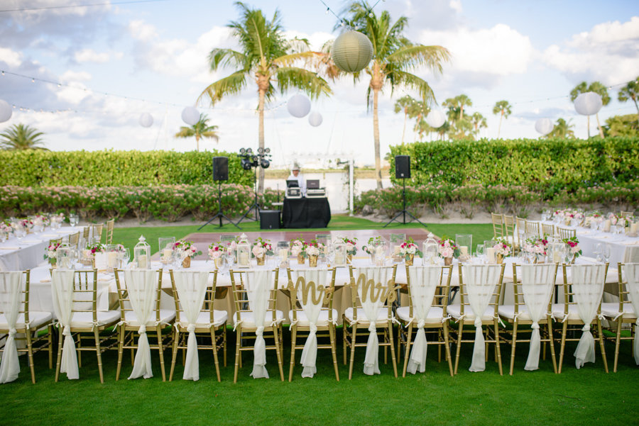 Outdoor Garden Wedding Reception with Long Feasting Tables with White Linens, Draped Gold Chiavari Chairs, Small Blush and Pink Centerpieces, Mr and Mrs Letters, Palm Trees Wrapped in String Lights with White and Gold Chinese Paper Lanterns | Sarasota Wedding Planner NK Productions | Venue Lonboat Key Club