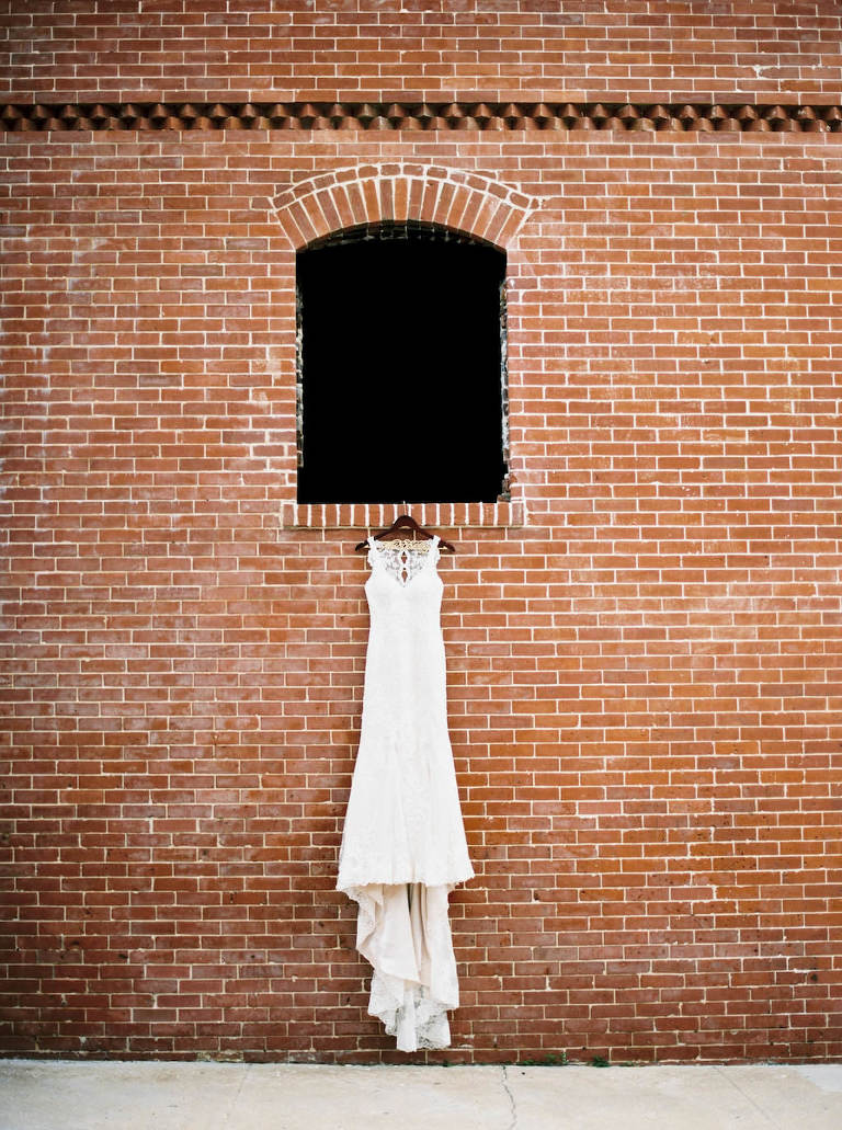 Illusion Lace Neckline Column Stella York Wedding Dress on Hanger against Brick Wall