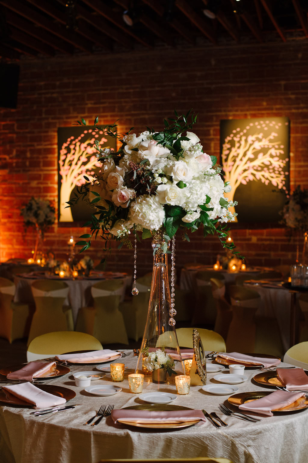 Gold and Pink Wedding Reception with Round Tables with Satin Linens, Gold Fabric Covered Chairs, Extra Tall Pink FLoral and Greenery Centerpieces in Glass Vases with Hanging Crystals
