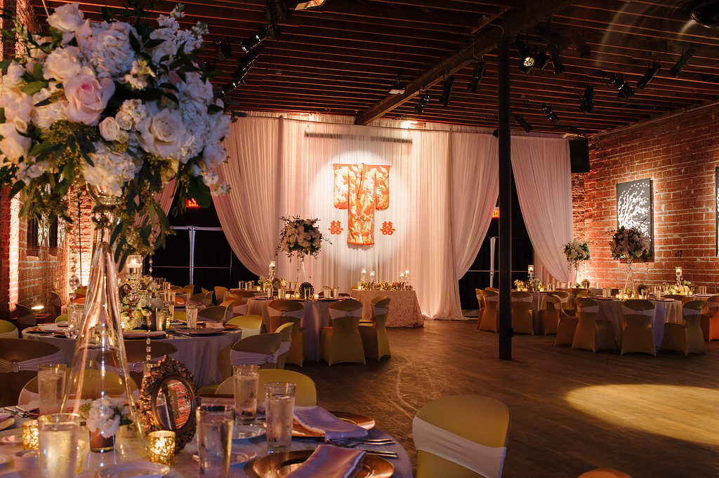 Gold and Pink Multicultural Wedding Reception with White Draping, Hanging Traditional Chinese Wedding Dress and Characters, Round Tables with Satin Linens, Gold Fabric Covered Chairs, Extra Tall Pink FLoral and Greenery Centerpieces in Glass Vases with Hanging Jewels | Downtown St Pete Unique Wedding Reception Venue NOVA 535