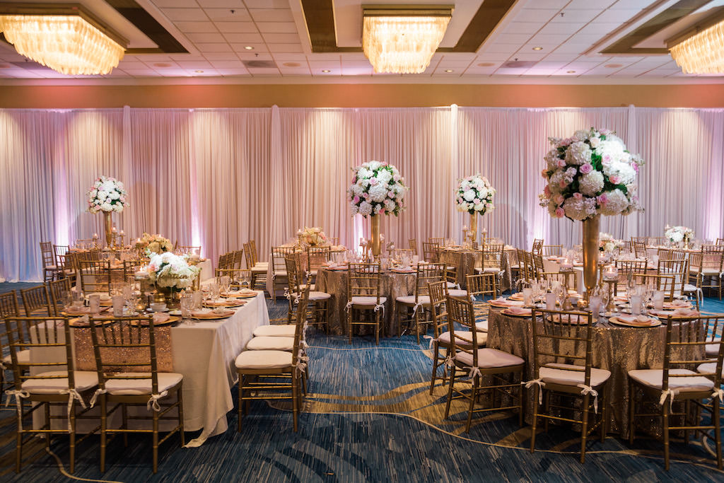Whimsical Gold and Pink Hotel Ballroom Wedding Reception with Tall White Hydrangea Pink Rose and Greenery Centerpieces in Gold Vases, Gold Sequin Table Cloths, and Gold Chiavari Chairs   Tampa Bay Wedding Draping, Linen, and Furniture Rental Gabro Event Services   Venue Hilton Clearwater Beach