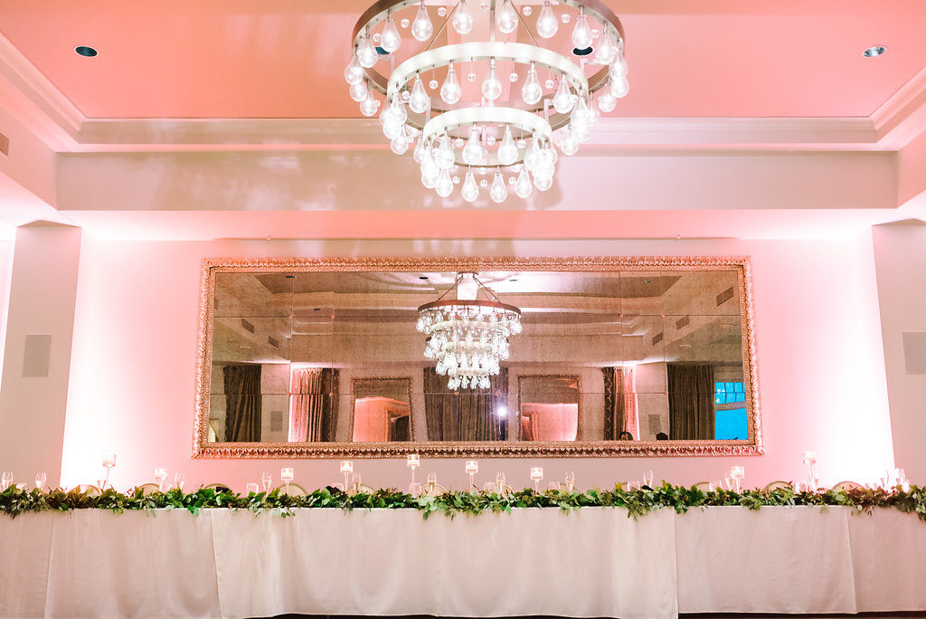 Ballroom Wedding Reception Feastign Table with Greenery Garland and Clear Glass Floating Votive Candle Holders and Chandelier | Downtown St Pete Historic Boutique Hotel Wedding Venue The BIrchwood
