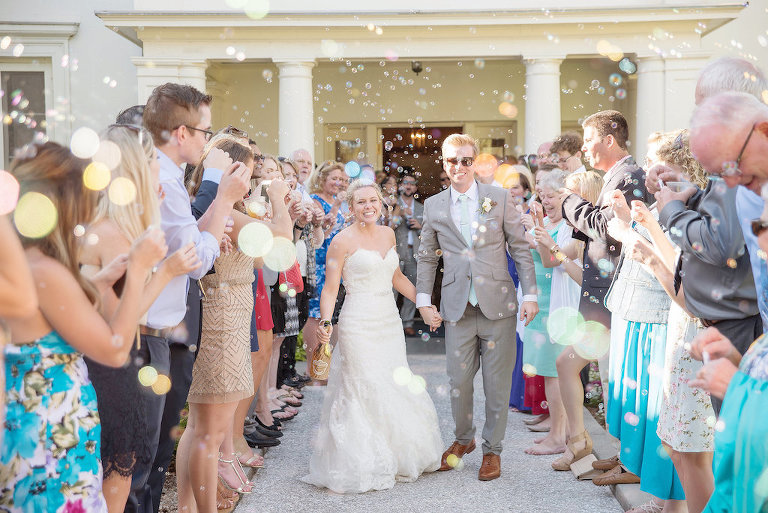 Outdoor Wedding Exit Portrait with Bubbles, Groom in Gray Suit with Brown Shoes and Mint Green Tie, Bride in Strapless Mermaid Lace Allure Bridals Dress | Sarasota Wedding Photographer Kristen Marie Photography