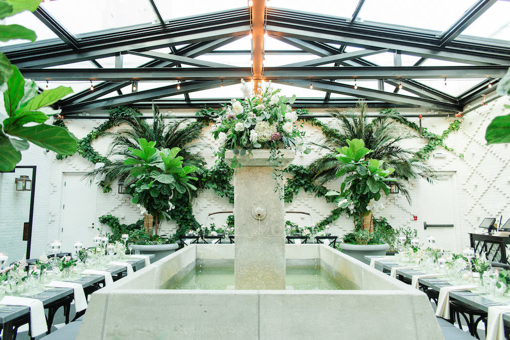 Indoor Ivory Garden Wedding Reception with Long Feasting Tables around Courtyard Fountain, Skylights, Stringlights, and Low White Floral and Greenery Centerpieces and Black Crossback Chairs | Vintage Tampa Wedding Venue The Oxford Exchange