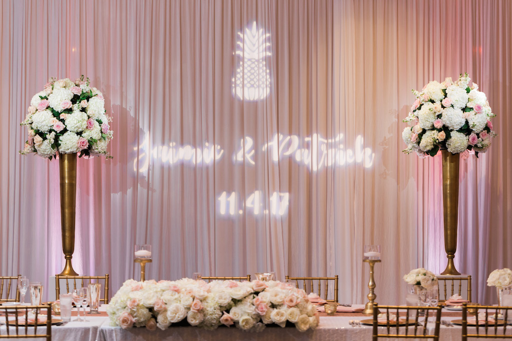 Pink and Gold Hotel Ballroom Wedding Reception With Custom Pineapple Projection on Pink Draping, Tall White Hydrangea, Pink Rose, and Greenery Centerpiece in Tall Gold Vases, Low Centerpiece with Stylish Gold Candlesticks, and Gold Chiavari Chairs   Tampa Bay Wedding Draping and Furniture Rentals Gabro Event Services