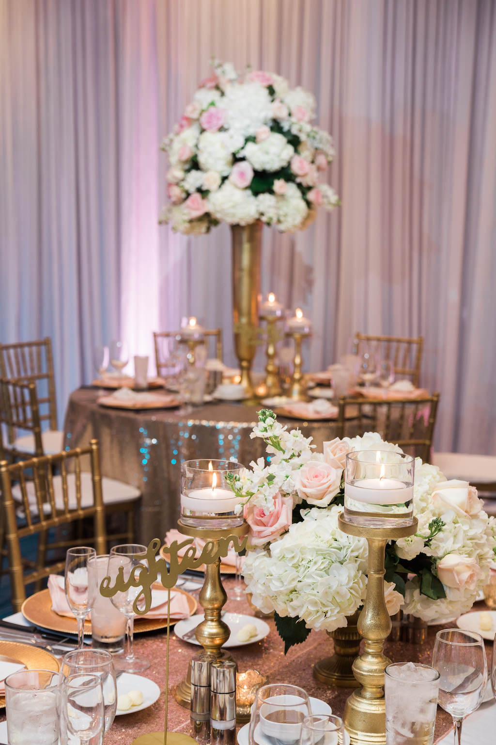 Whimsical Gold and Pink Hotel Ballroom Wedding Reception with Tall White Hydrangea Pink Rose and Greenery Centerpieces in Gold Vases, Gold Sequin Table Cloths, and Gold Chiavari Chairs and Stylish Gold Candlestick Holders and Table Numbers   Tampa Bay Wedding Draping, Linen, and Furniture Rental Gabro Event Services   Venue Hilton Clearwater Beach