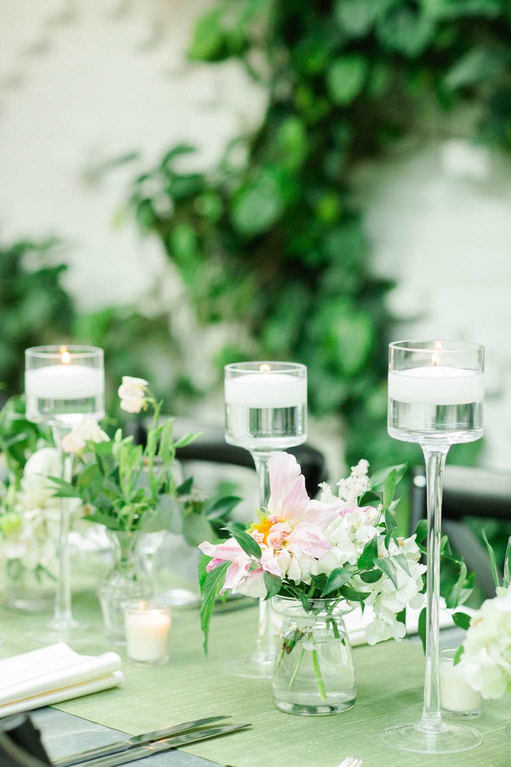 Indoor Ivory Garden Wedding Reception Industrial Metal Feasting Table with Low Pink and White Floral with Greenery Centerpieces in Glass Jars, and Floating Votive Candles in Tall Glass Holders   Downtown Tampa Wedding Venue The Oxford Exchange