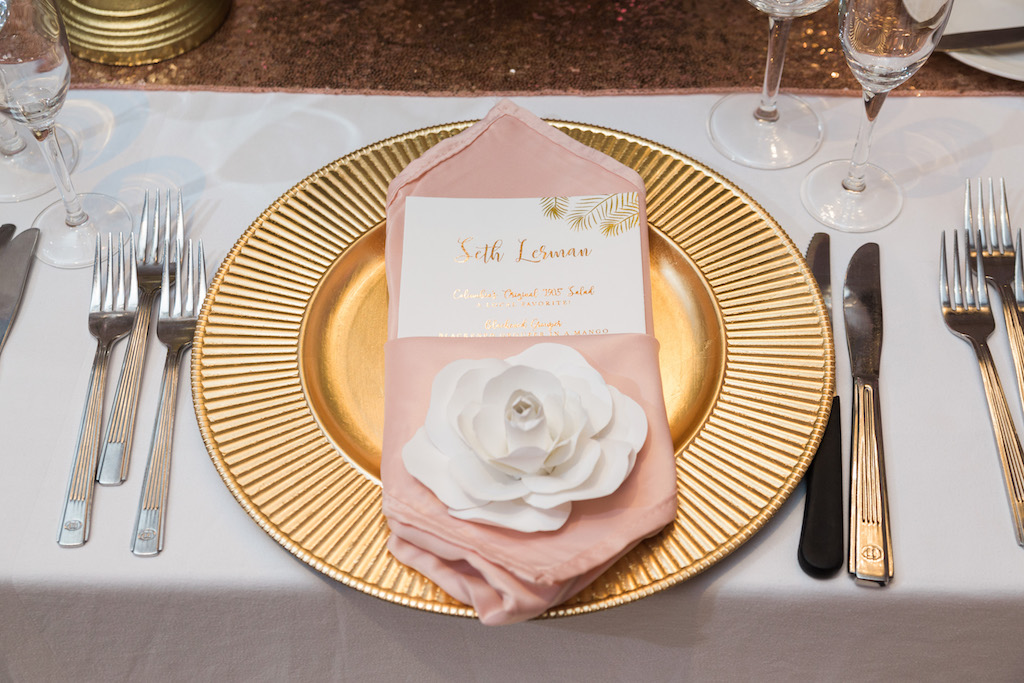 Whimsical Wedding Reception Table Setting with Gold Charger and White Paper Flower, Pink Napkin, and Tropical Gold Foil Printed Menu with Pink Sequin Linen