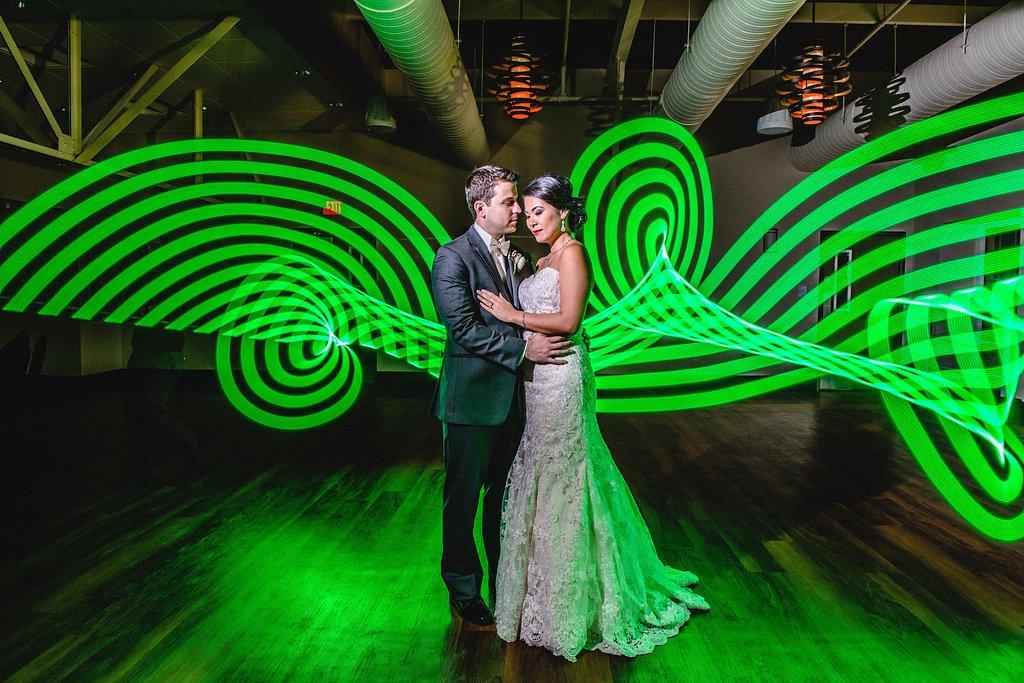 Creative Industrial Indoor Bride and Groom Portrait, Bride in Lace Column Strapless Dress, Groom in Gray Tuxedo, with Neon Green Light Art   Downtown St. Pete Wedding Venue NOVA 535