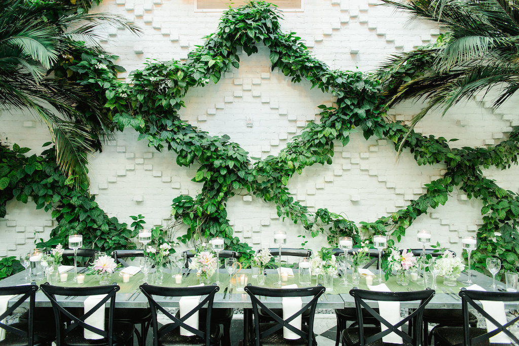 Indoor Ivory Garden Wedding Reception Industrial Metal Feasting Table with Low Pink and White Floral with Greenery Centerpieces, Black Crossback Chairs, and Floating Votive Candles in Tall Glass Holders   Downtown Tampa Wedding Venue The Oxford Exchange