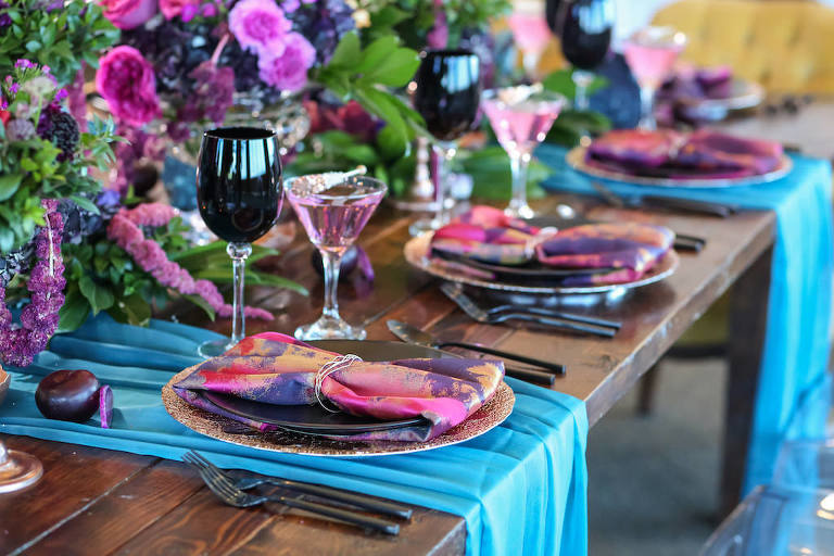 Vibrant Whimsical Wedding Reception Wooden Feasting Table with Black Flatware, Wine Glasses, and Plates, Copper Chargers and Votive Candleholders, Low Plum and Fuchsia Florals with Greenery Centerpieces, Pink and Purple Watercolor Napkins and Turquoise Linen Runners, Glitter Rock Candy Favors | Tampa Bay Wedding Planner Kelly Kennedy Weddings and Events | Furniture Rentals A Chair Affair | Florist Gabro Event Services