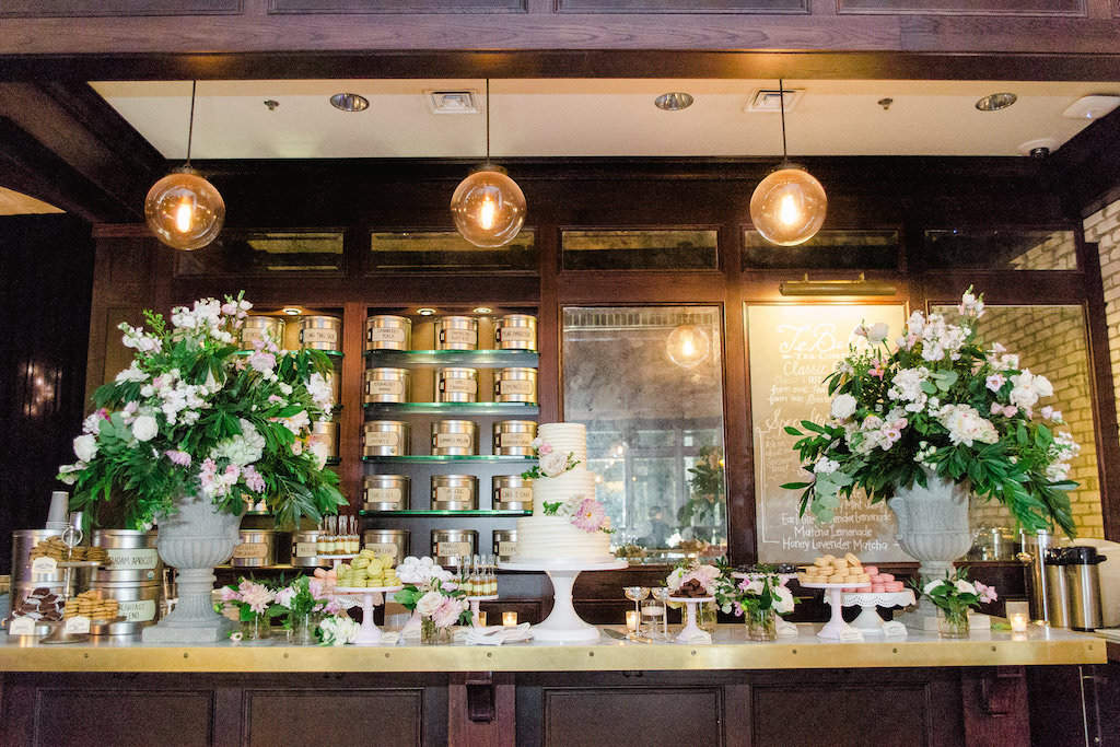 Indoor Vintage Ivory Garden Wedding Reception Dessert Bar with Tall Blush Pink and White Floral with Greenery in Stone Planters, Three Tier Round White Wedding Cake with Pink Flowers on White Cake Stand, and Macaroons, Cake Shooters, Cookies on Mismatched Stands   Downtown Tampa Venue The Oxford Exchange