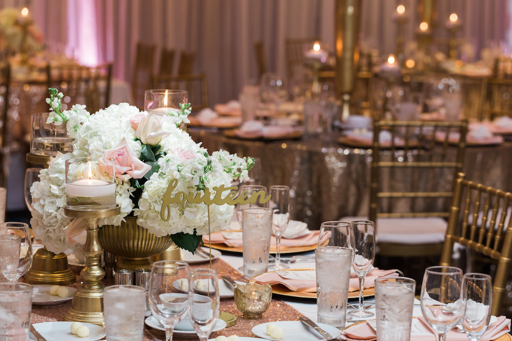 Whimsical Gold and Pink Hotel Ballroom Wedding Reception with Low White Hydrangea Pink Rose and Greenery Centerpieces in Gold Vases, Gold Sequin Table Cloths, and Gold Chiavari Chairs and Stylish Gold Candlestick Holders and Table Numbers   Tampa Bay Wedding Draping, Linen, and Furniture Rental Gabro Event Services   Venue Hilton Clearwater Beach