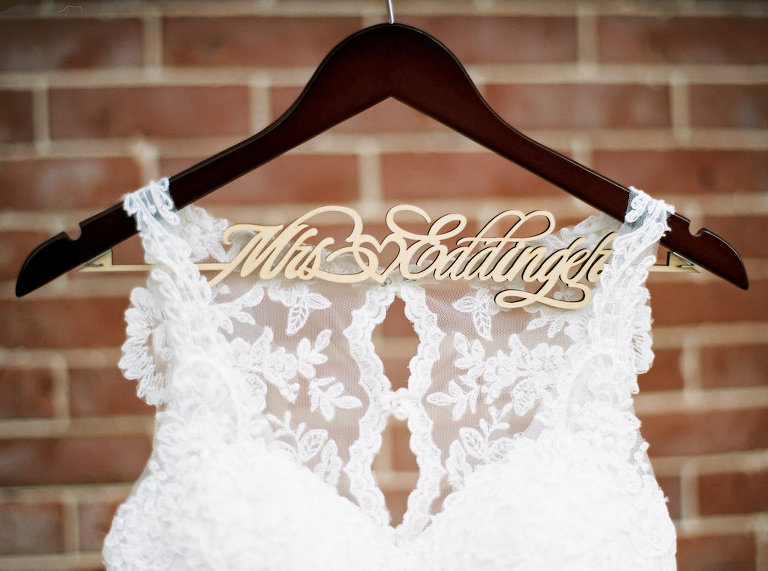 Illusion Lace Neckline Column Stella York Wedding Dress on Custom Gold and Wood Hanger against Brick Wall
