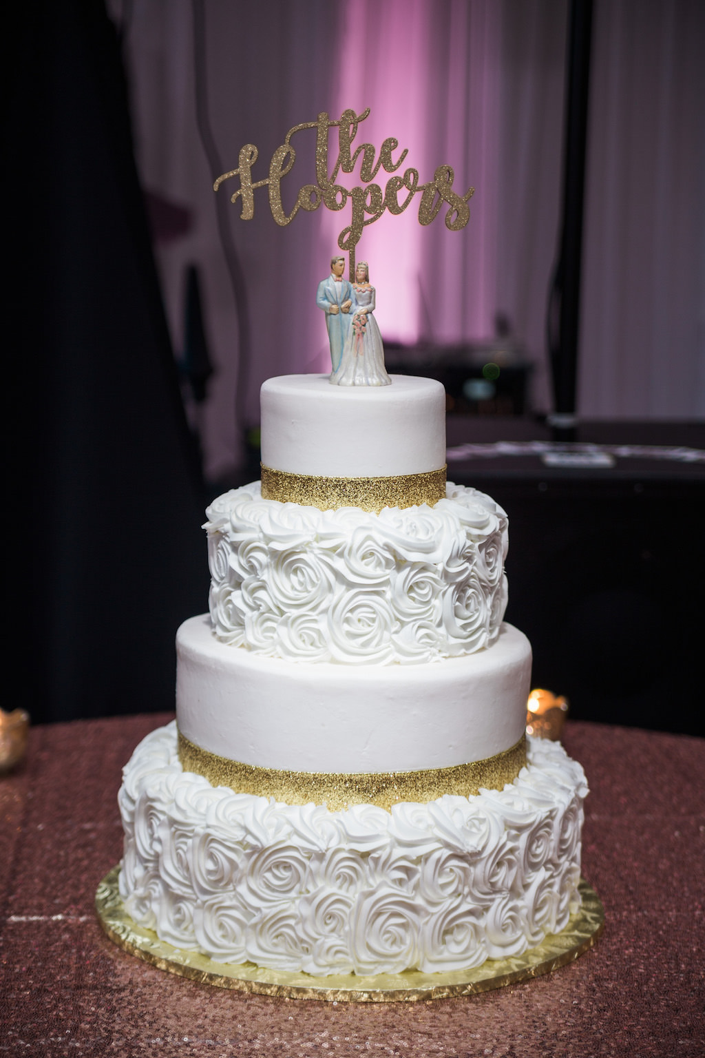 Four Tier Round White with Gold Glitter and Rose Icing Wedding Cake on Flat Gold Cake Stand and Rose Gold Glitter Linen, with Custom Figurine Cake Topper and Gold Couple Name