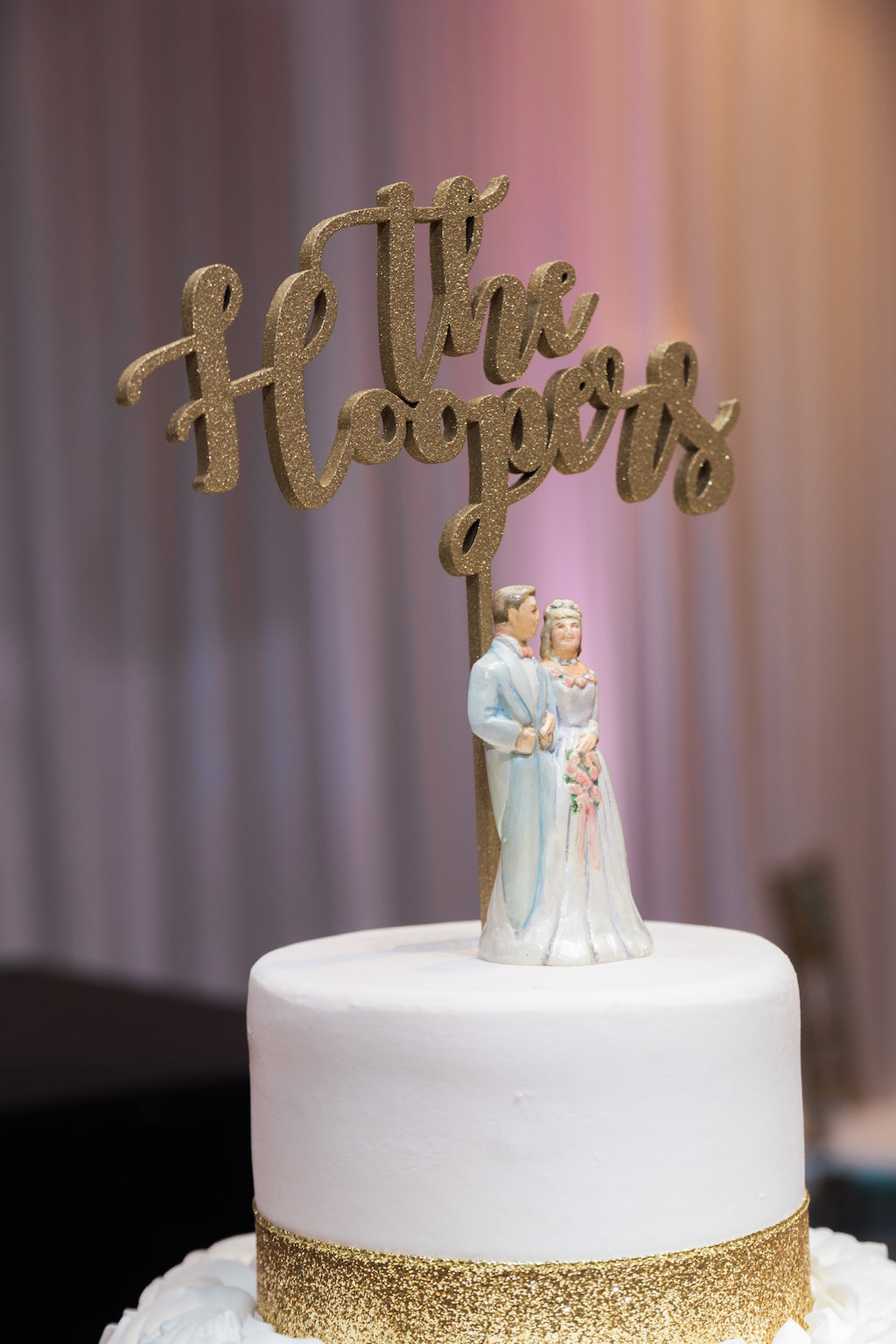 Four Tier Round White with Gold Glitter and Rose Icing Wedding Cake with Custom Figurine Cake Topper and Gold Couple Name