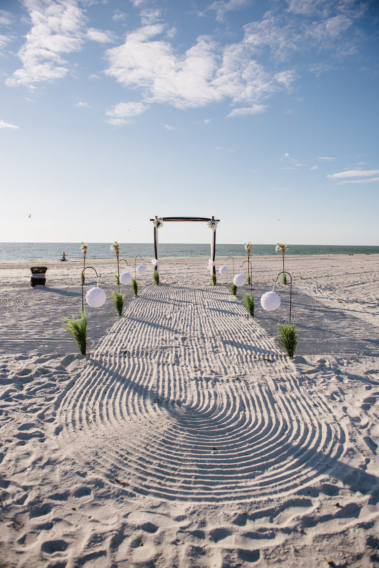 Simple Intimate Beach Wedding Ceremony Decor with White Pomander Balls on Iron Hook with Greenery, Black Tulle Draped Table, Wooden Arch with White FLowers and Draping, and Tiki Torches | Tampa Bay Wedding Planner Gulf Beach Weddings | Treasure Island Venue Sunset Vista Condo Hotel Resort