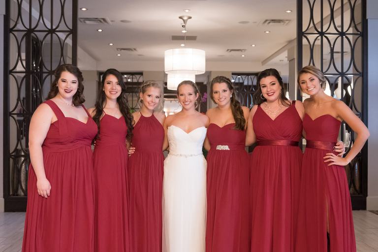 Hotel Interior Bridal Party Portrait, Bride in Strapless Belted Maggie Sottero Wedding Dress, Bridesmaids in Mismatched Burgundy Red Azazie Dresses | Tampa Wedding Photographer Carrie Wildes Photography