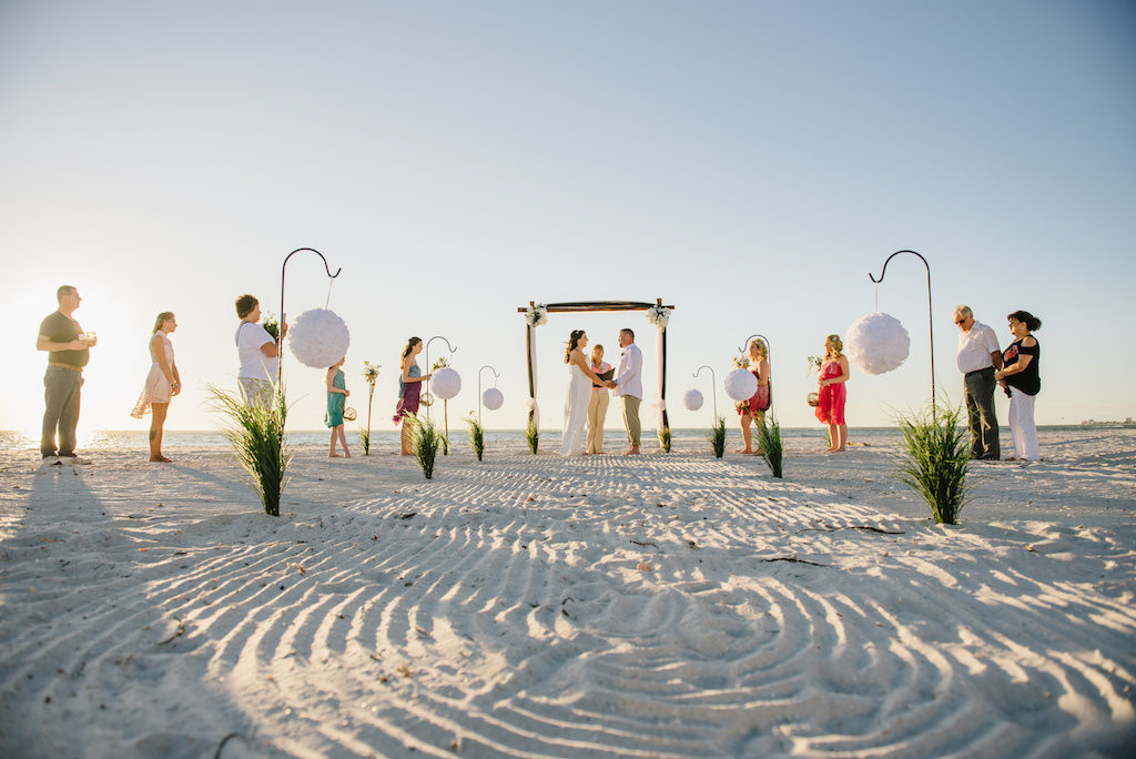 Simple Intimate Beach Wedding Ceremony Portrait with White Pomander Balls on Iron Hook with Greenery, Black Tulle Draped Table, Wooden Arch with White Flowers and Draping, and Tiki Torches, Bridesmaids in Mismatched Bright Colored Tropical Dresses   Tampa Bay Wedding Planner Gulf Beach Weddings   Treasure Island Venue Sunset Vista Condo Hotel Resort