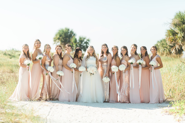 Outdoor Beachfront Bridal Party Portrait in Mismatched Pink, Blush, Rose Gold Sequin Mismatched Bella Bridesmaids Dresses, Bride in Halter Ballgown Hayley Paige Dress, with White Floral Bouquets with Long Ribbons | Clearwater Beach Wedding