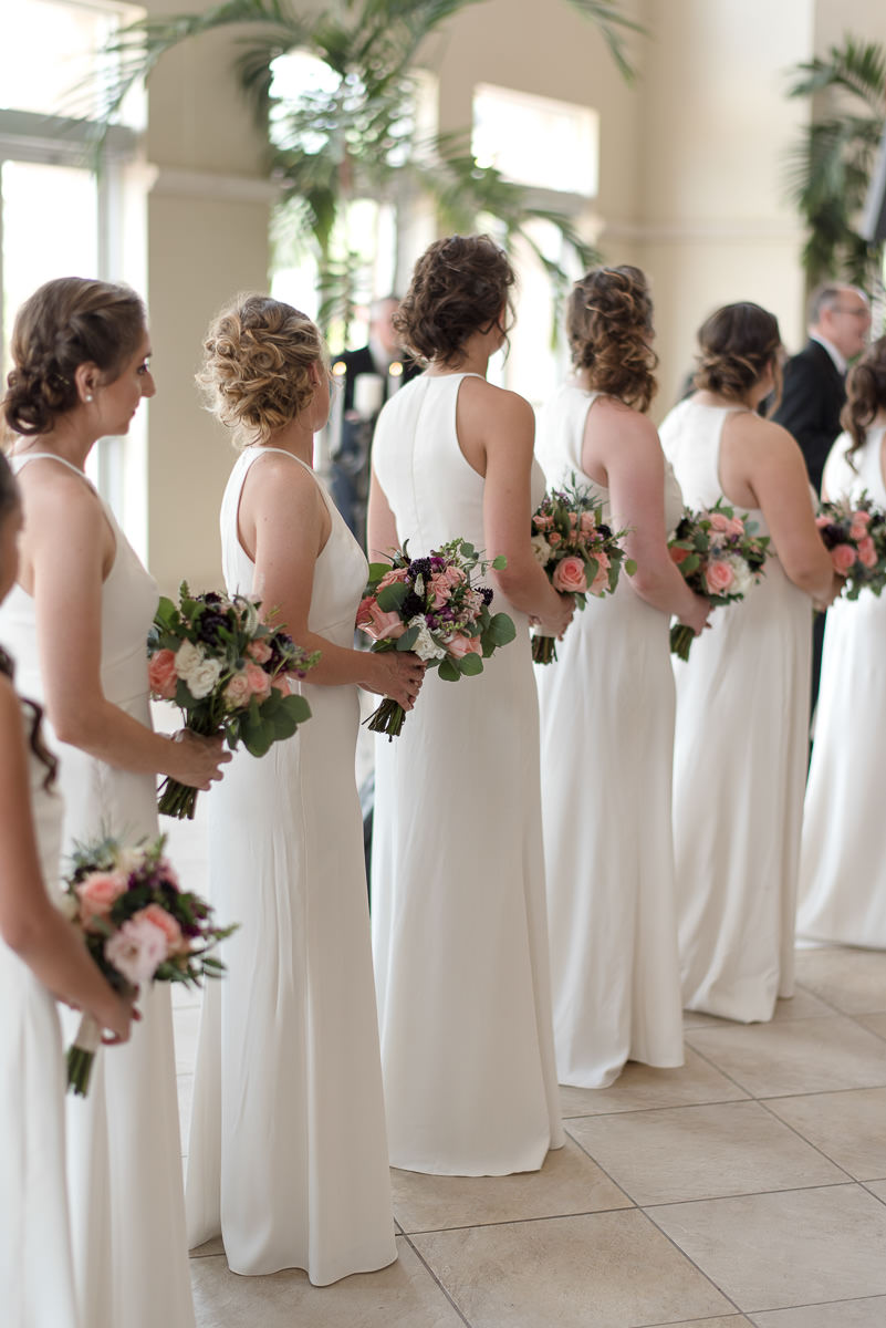 Wedding Ceremony Bridal Party Portrait, Bridesmaids in Halter Floor length White Dessy Dresses with Pink, Peach, Purple and White Floral Bouquets with Greenery | Tampa Bridesmaid Dress Shop Bella Bridesmaids