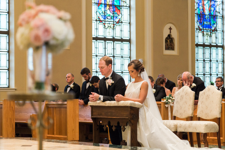 Traditional Church Wedding Ceremony Portrait, with White Floral and Greenery with Ribbon Flowers on Wooden Pews | St Pete Ceremony Venue St Paul's Catholic Church
