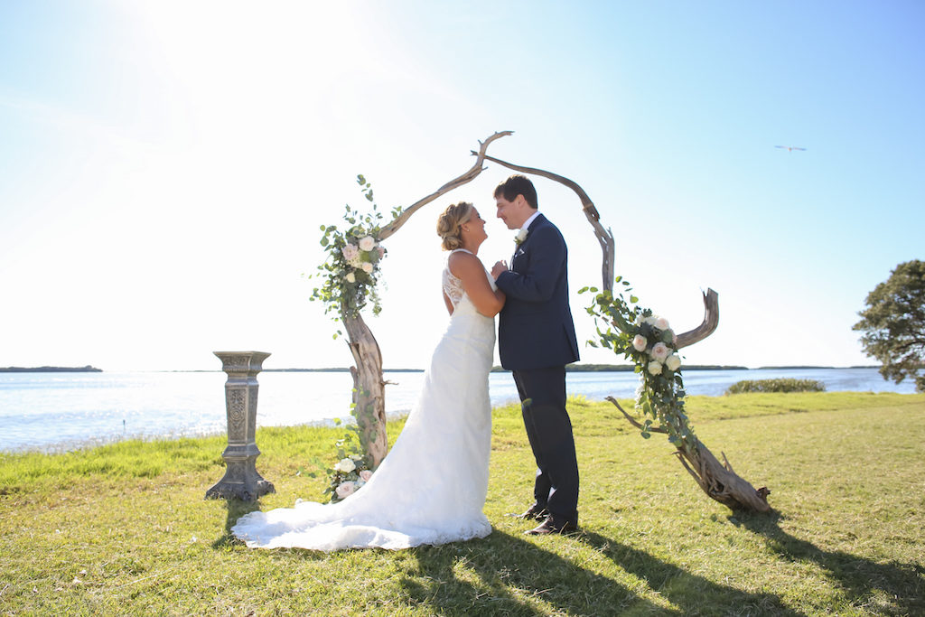 Outdoor Waterfront Wedding Ceremony Portrait with Organic Driftwood Arch with White Rose and Natural Greenery Florals, Bride in Lace Open Back Column Dress with Train | Venue Tampa Bay Watch | St Petersburg Wedding Photographer Lifelong Photography Studio