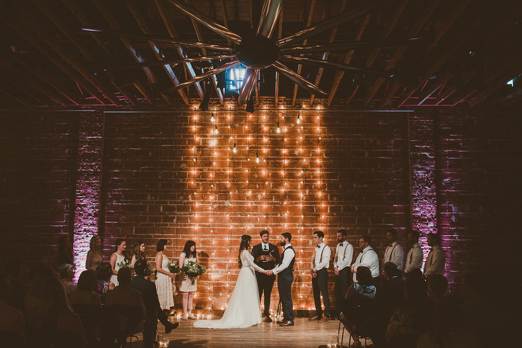 Dramatic Minimalist Indoor Wedding Ceremony Portrait with Hanging Edison Bulb String Light Backdrop on Exposed Brick, Bridesmaids in Blush Pink with Greenery Bouquets, Groomsmen in White Shirts with Suspenders and Bow Ties, Groom in Navy Blue Vest   Unique Downtown St Pete Wedding Venue NOVA 535