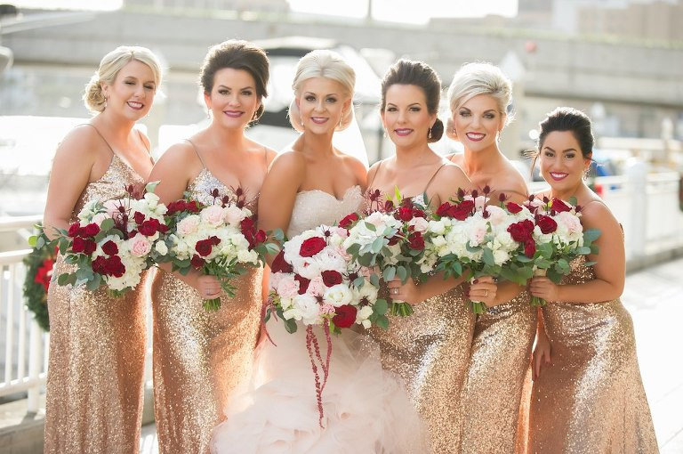 Outdoor Waterfront Bridal Party Portrait, Bridesmaids in Gold Sequin Spaghetti Strap Dresses, Bride iN Strapless Blush Mermaid Dress, with Red and Blush Pink Rose with Greenery Bouquets | Tampa Bay Wedding Photographer Andi Diamond Photography | Hair and Makeup Michele Renee The Studio | Bridesmaids Dress Shop Bella Bridesmaids