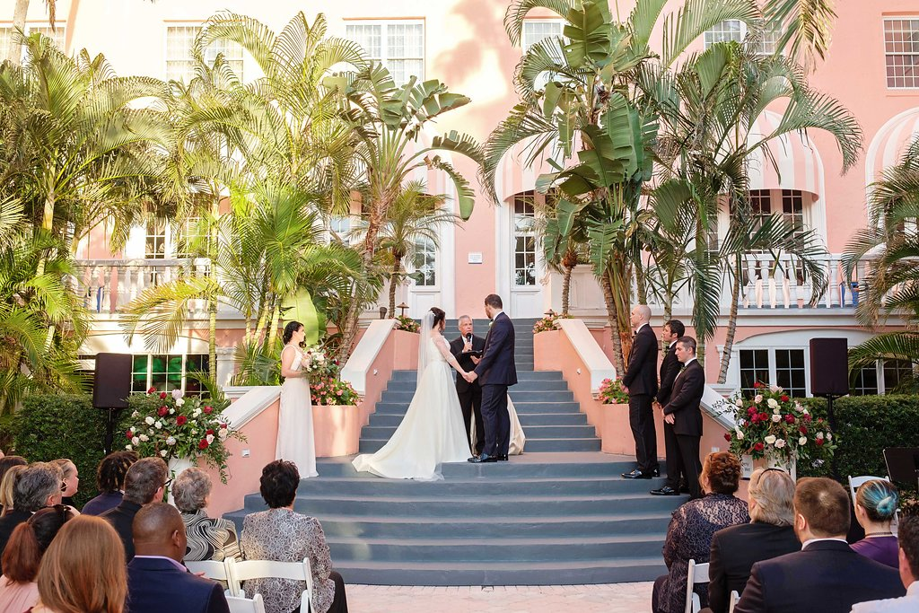 Outdoor Hotel Courtyard Wedding Ceremony Portrait with Red and White Rose Florals with Greenery | Historic Waterfront Hotel St. Pete Beach Wedding Venue The Don CeSar | Photographer Marc Edwards Photographs | Planner Parties A La Carte