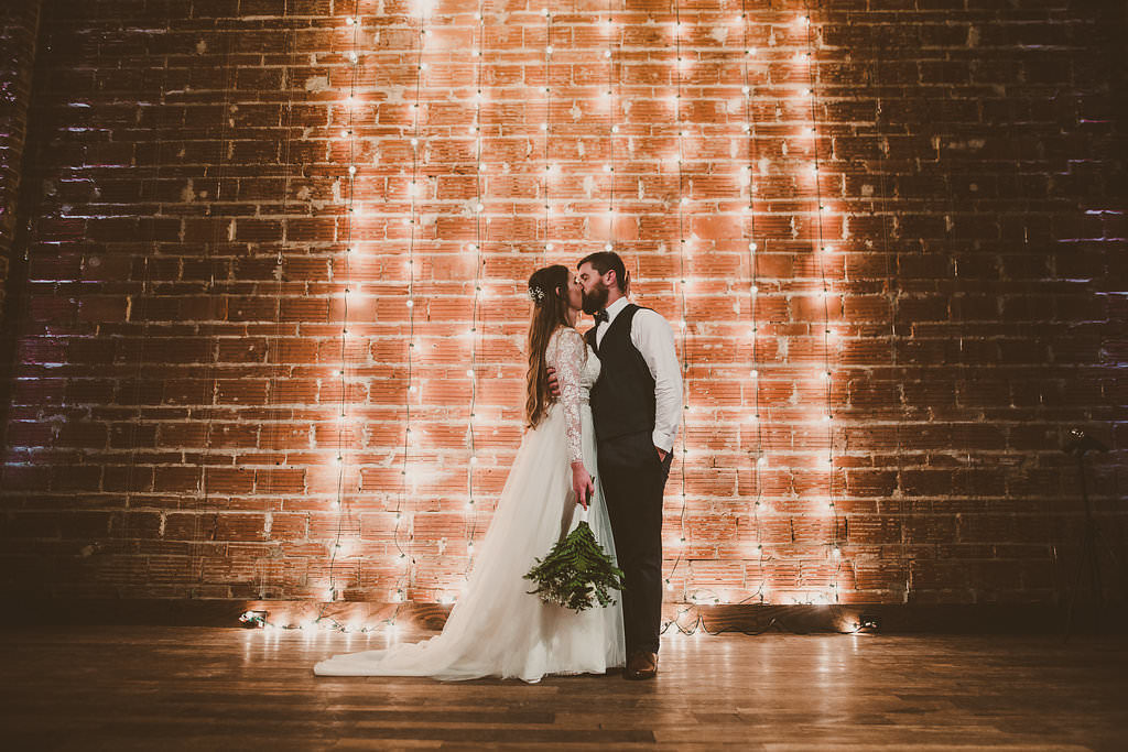 Dramatic Minimalist Indoor Wedding Ceremony First Kiss Portrait with Hanging Edison Bulb String Light Backdrop on Exposed Brick, Bride in Long Sleeve Davids Bridal Dress with Green Fern Bouquet, Groom in Navy Blue Vest and Bow Tie | Unique Downtown St Pete Wedding Venue NOVA 535