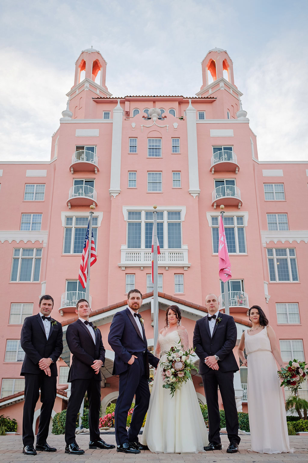 Outdoor Wedding Party Portrait, Groom in Navy Suit, Groomsmen in Black, Bridesmaid in Simple White Belted Column Dress, Bride with Pink Portea, Blush and White Floral with Greenery Bouquet in front of Historic St. Pete Beach Waterfront Hotel The Don CeSar | Photographer Marc Edwards Photographs
