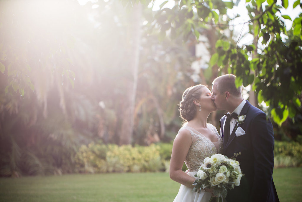 Outdoor Hotel Garden Wedding Portrait, Bride in Beaded Dress with White Rose and Greenery Bouquet and Silver Floral Hair Accessory, Groom in Navy Suit with White Floral Boutonniere and Black Bow Tie | Sarasota Wedding Photographer Cat Pennenga Photography