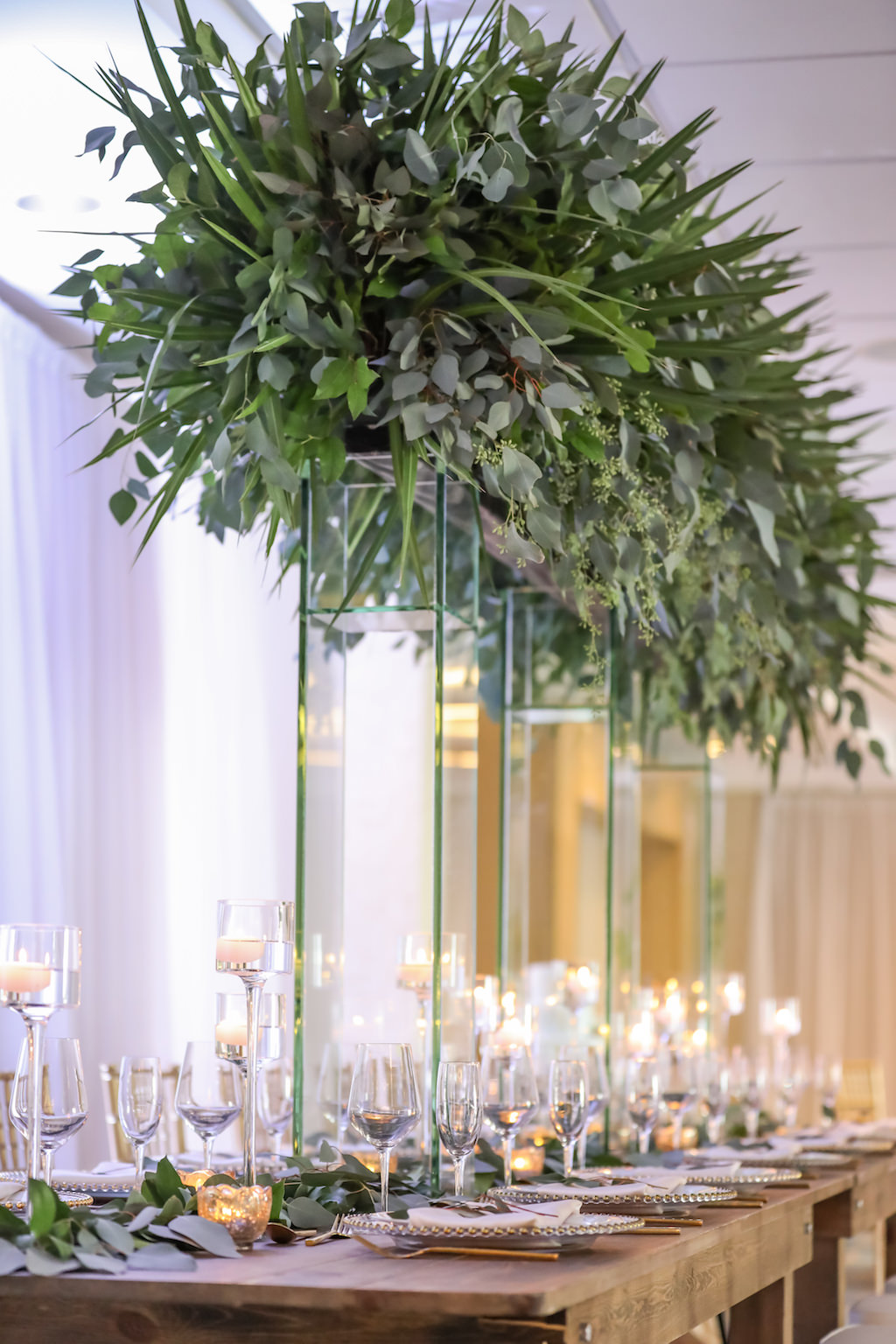 Hotel Ballroom Wedding Reception With Long Wood Feasting Table, Extra Tall Greenery Centerpiece in Clear Glass Rectangular Vases, Gold Chiavari Chairs, White Draping, and Glass Candleholders at Varying Heights and Gold Beaded Glass Chargers   Beach Hotel Wedding Venue Hilton Clearwater Beach
