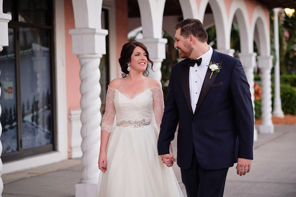 Outdoor Bride and Groom Wedding Portrait, Groom in Black and Navy Blue Tuxedo with White Floral and Greenery Boutonniere, Bride in Lace Sleeve Silver Belted A Line Wedding Dress | St Pete Beach Wedding Venue The Don CeSar | Tampa Bay Photographer Marc Edwards | Bridal Hair and Makeup Femme Akoi Studio