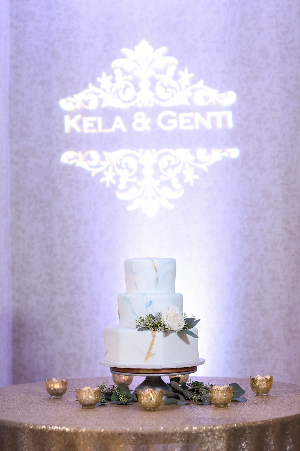 Three Tier Round White Blue and Gold Marble Wedding Cake with White ROse and Greenery on Gold Cake Stand, with Custom GOBO Projection, and Gold Sequin Linen with Votive Candles   Tampa Bay Waterfront Hotel Wedding Venue Hilton Clearwater Beach