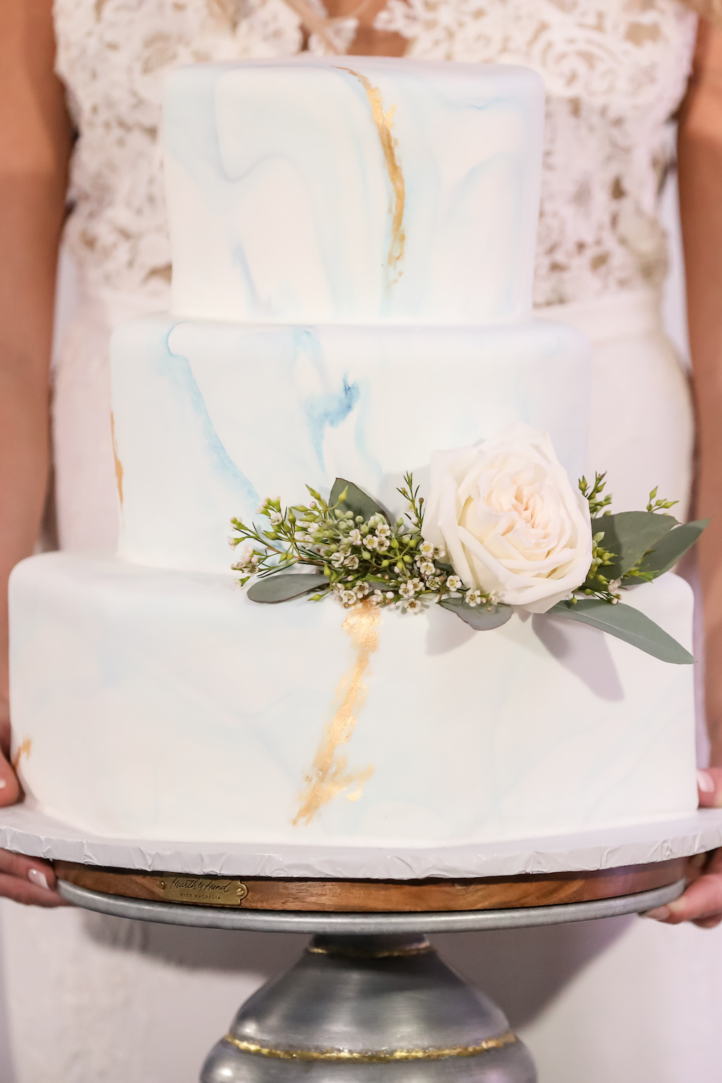 Three Tier Round Blue and Gold White Marble Wedding Cake on Silver Cake Stand, with White Rose and Greenery