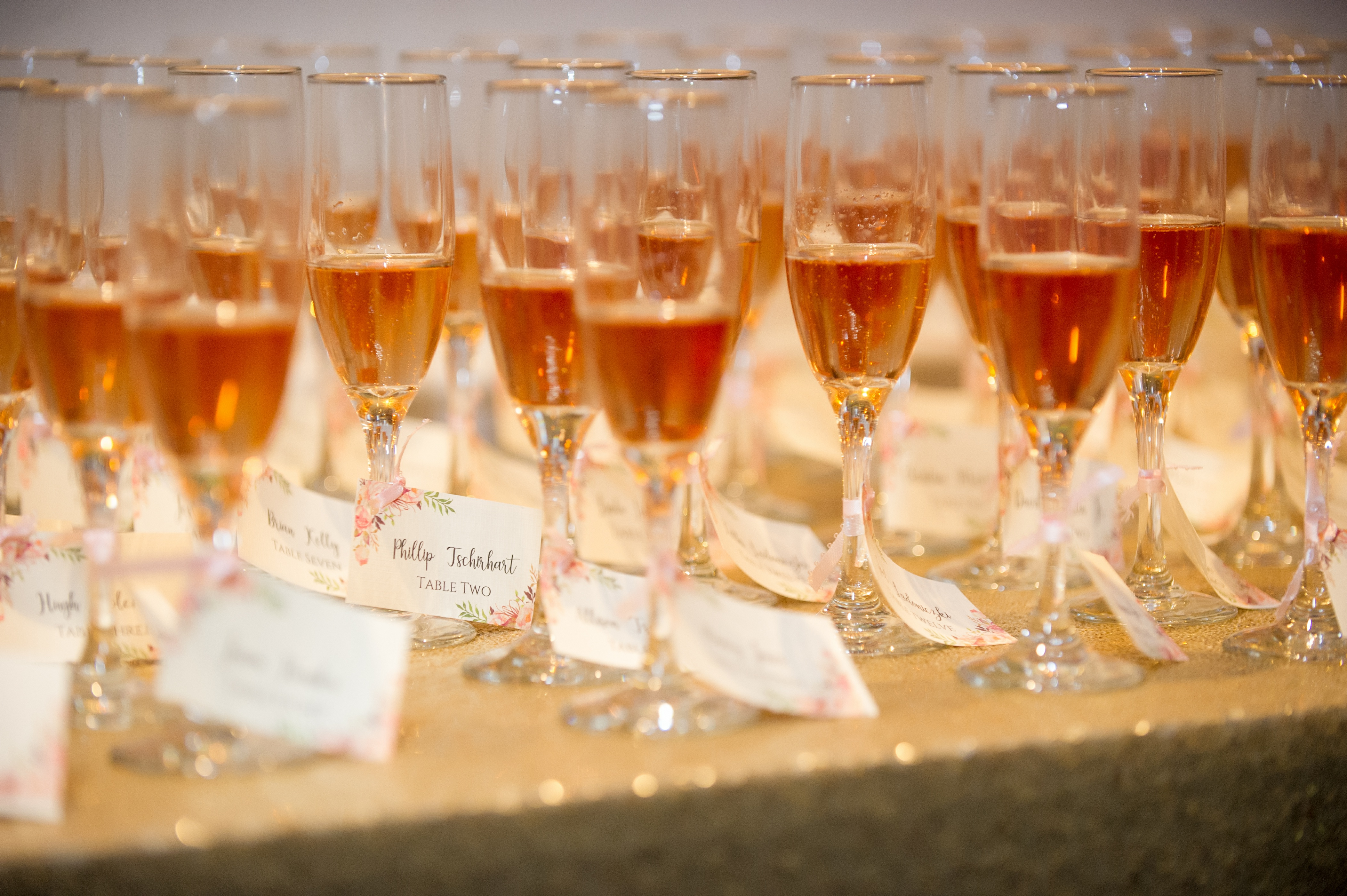 Rose Champagne Glass Escort Card Table with Gold Sequin Linen, with Pink Watercolor and Black Script Printed Cards tied with Pink Ribbon