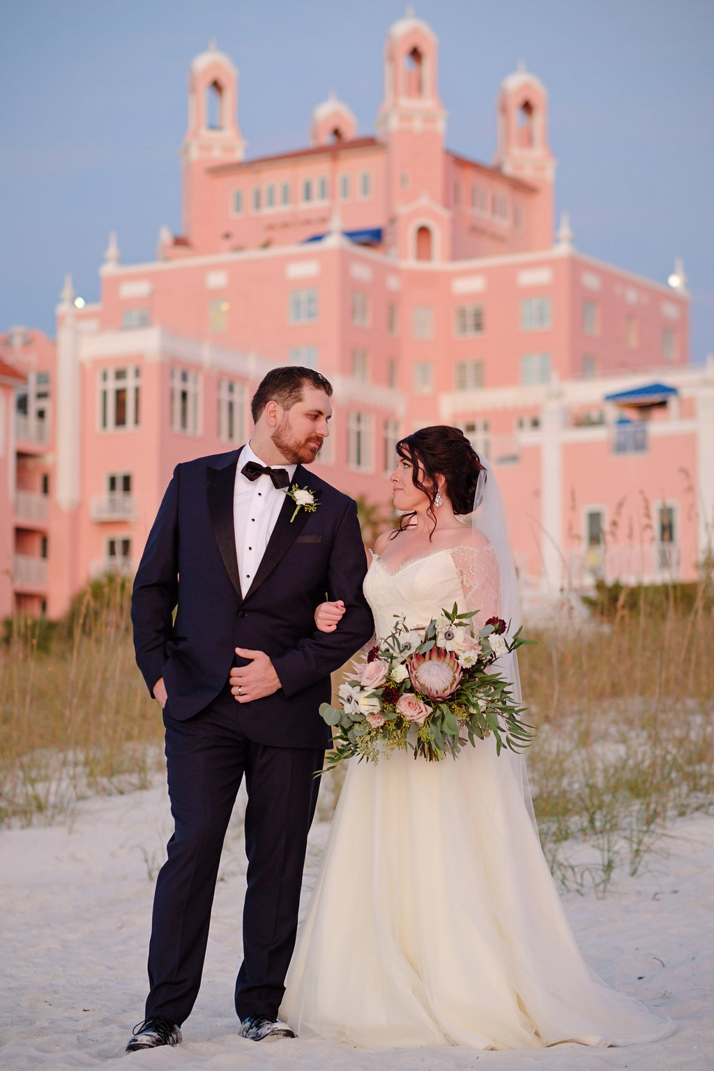 Outdoor Beach Sunset Bride and Groom Wedding Portrait in A Line Wedding Dress with White, Pink, and Burgundy with Greenery Bouquet, Bride in Navy and Black Tuxedo with White Floral Boutonniere | St Petersburg Wedding Photographer Marc Edwards Photography | Hair and Makeup Femme Akoi Beauty Studio | Historic St Pete Waterfront Hotel Wedding Venue The Don CeSar