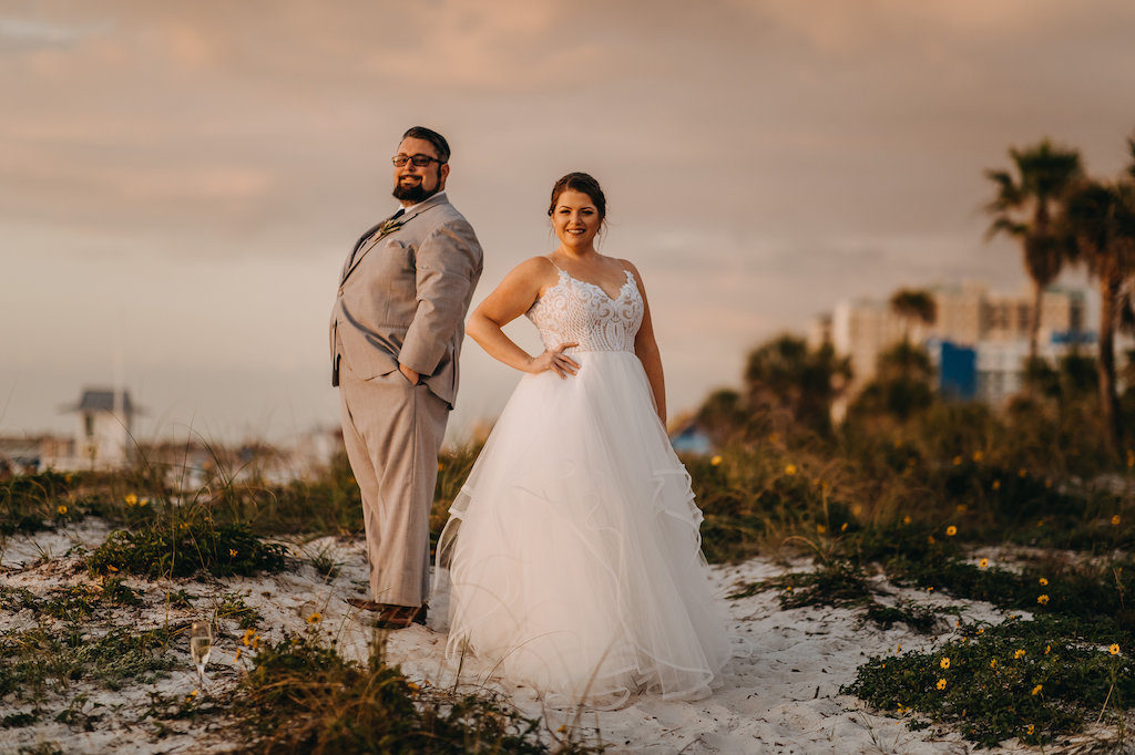Outdoor Beach Sunset Wedding Portrait, Bride in Patterned Bodice Spaghetti Strap Ballgown Hayley Paige Dress, Groom in Gray Suit with BLack Tie and White with Greenery Boutonniere | Clearwater Beach Wedding Photographer Rad Red Creative | Bridal Hair and Makeup Femme Akoi Beauty Studio