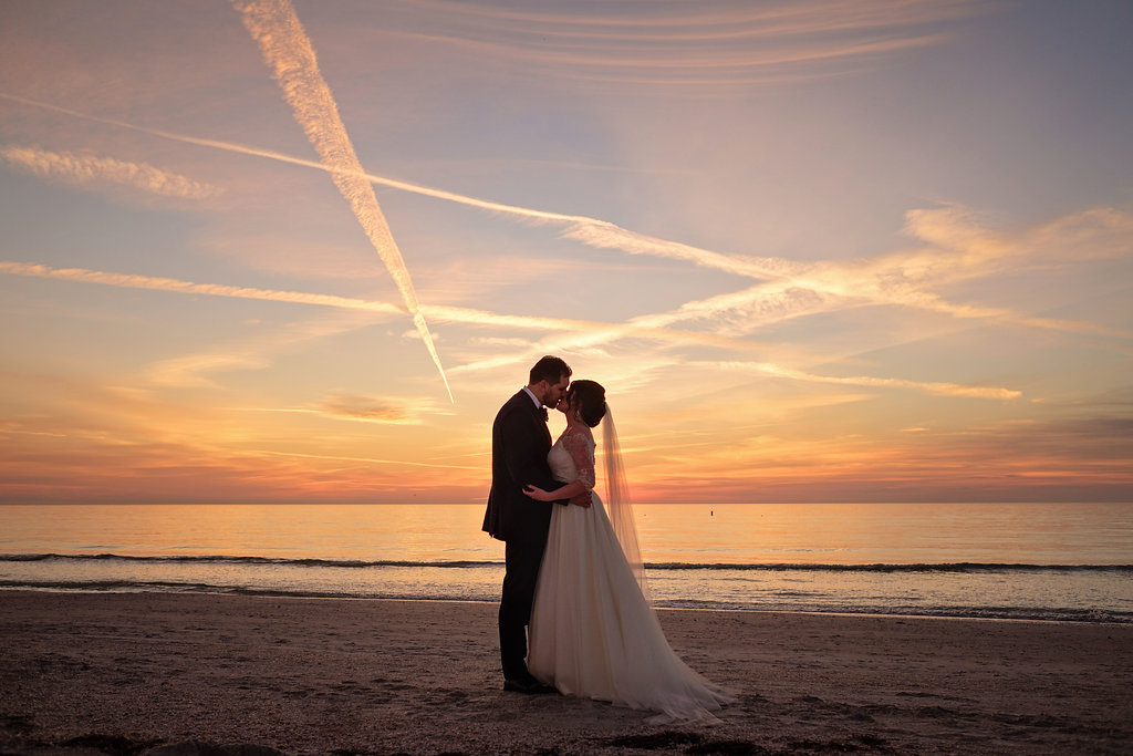 Outdoor Beach Sunset Bride and Groom Wedding Portrait, Bride in Lace Sleeve Silver Belted A Line Wedding Dress | St Pete Beach Wedding Venue The Don CeSar | Tampa Bay Photographer Marc Edwards | Bridal Hair and Makeup Femme Akoi Studio